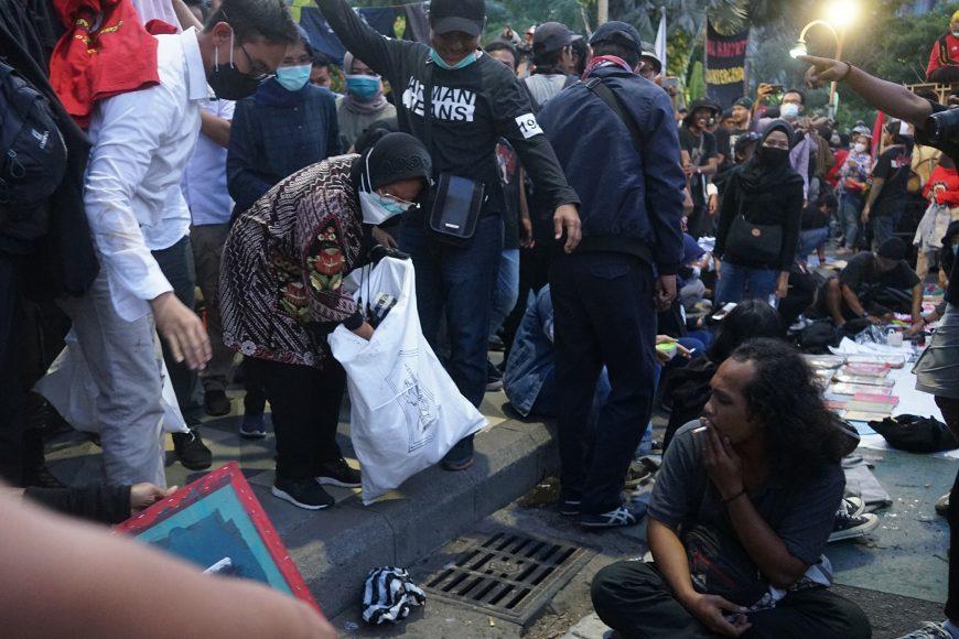 Sembari membawa karung, Wali Kota Surabaya Tri Rismaharini tampak memunguti sampah yang ada di antara pendemo /Ist